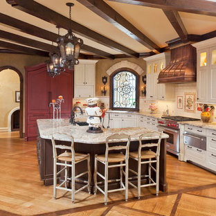 Eat-in kitchen - traditional l-shaped medium tone wood floor eat-in kitchen idea in Houston with granite countertops, a farmhouse sink, white cabinets, white backsplash, paneled appliances and an island
