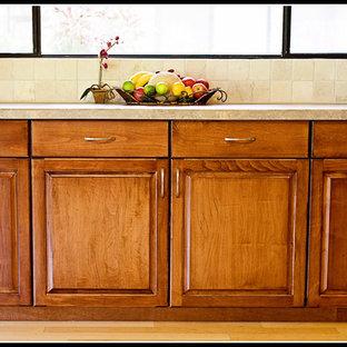Cette photo montre une grand cuisine ouverte linéaire chic avec un placard à porte plane, des portes de placard en bois sombre, un plan de travail en marbre, une crédence beige, un électroménager en acier inoxydable, un îlot central, un sol beige et un plan de travail rose.