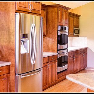 ワシントンD.C.の広いトラディショナルスタイルのおしゃれなキッチン (フラットパネル扉のキャビネット、濃色木目調キャビネット、大理石カウンター、ベージュキッチンパネル、シルバーの調理設備、ベージュの床、ピンクのキッチンカウンター) の写真
