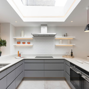 This is an example of a medium sized contemporary u-shaped kitchen in London with a double-bowl sink, flat-panel cabinets, composite countertops, white splashback, ceramic splashback, concrete flooring, grey floors, grey cabinets, black appliances and a breakfast bar.