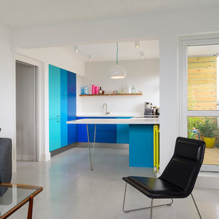 This is an example of a small contemporary u-shaped open plan kitchen in London with flat-panel cabinets, blue cabinets and a breakfast bar.