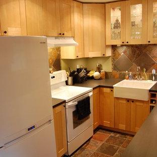 シンシナティの小さいエクレクティックスタイルのおしゃれなコの字型キッチン (エプロンフロントシンク、シェーカースタイル扉のキャビネット、淡色木目調キャビネット、ラミネートカウンター、マルチカラーのキッチンパネル、石タイルのキッチンパネル、白い調理設備、スレートの床、アイランドなし) の写真