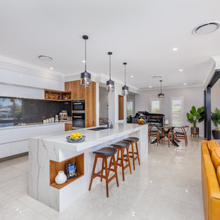 Design ideas for a contemporary l-shaped kitchen in Brisbane with flat-panel cabinets, white cabinets, stainless steel appliances, with island, beige floor and white benchtop.