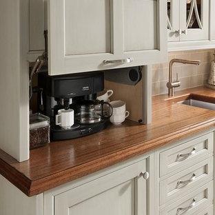 Exempel på ett litet klassiskt linjärt kök och matrum, med en undermonterad diskho, luckor med infälld panel, grå skåp, träbänkskiva, grått stänkskydd, stänkskydd i glaskakel, svarta vitvaror och vinylgolv