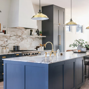Inspiration for a mid-sized transitional galley open plan kitchen in Calgary with a double-bowl sink, shaker cabinets, blue cabinets, marble benchtops, multi-coloured splashback, marble splashback, panelled appliances, light hardwood floors, with island and multi-coloured benchtop.