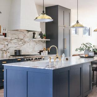 カルガリーの中サイズのトランジショナルスタイルのおしゃれなキッチン (ダブルシンク、シェーカースタイル扉のキャビネット、青いキャビネット、大理石カウンター、マルチカラーのキッチンパネル、大理石のキッチンパネル、パネルと同色の調理設備、淡色無垢フローリング、マルチカラーのキッチンカウンター) の写真