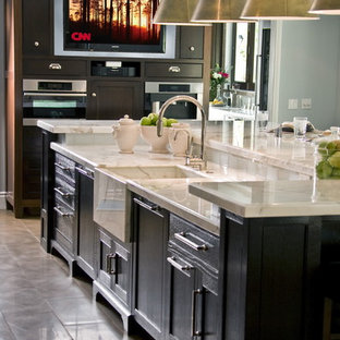 This is an example of a traditional kitchen in Los Angeles with an integrated sink, recessed-panel cabinets, dark wood cabinets and marble benchtops.