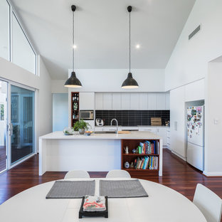 Inspiration for a contemporary l-shaped open plan kitchen in Perth with flat-panel cabinets, white cabinets, black splashback, subway tile splashback, stainless steel appliances, medium hardwood floors, with island and brown floor.