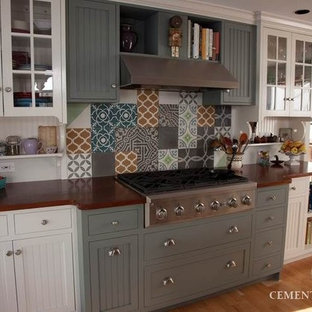 Inspiration for a large timeless kitchen remodel in Tampa with white cabinets, stainless steel appliances, marble countertops and an island