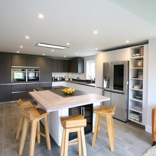 Inspiration for a medium sized contemporary l-shaped open plan kitchen in Buckinghamshire with a submerged sink, flat-panel cabinets, stainless steel appliances, an island, grey floors and black worktops.