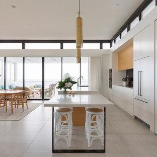 シドニーのコンテンポラリースタイルのおしゃれなキッチン (ドロップインシンク、黒い調理設備、セラミックタイルの床、グレーの床、フラットパネル扉のキャビネット、白いキャビネット、大理石カウンター、マルチカラーのキッチンカウンター、ミラータイルのキッチンパネル) の写真