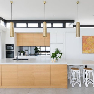This is an example of a contemporary galley eat-in kitchen in Sydney with black appliances, ceramic floors, grey floor, an undermount sink, flat-panel cabinets, medium wood cabinets, mirror splashback, with island, marble benchtops and multi-coloured benchtop.