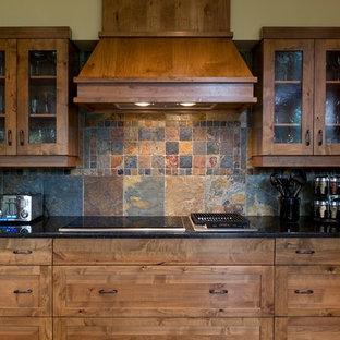 カルガリーのトラディショナルスタイルのおしゃれなキッチン (マルチカラーのキッチンパネル、シェーカースタイル扉のキャビネット、中間色木目調キャビネット、スレートの床) の写真