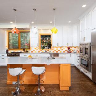 Cette image montre une cuisine bohème en L avec un évier encastré, un placard à porte shaker, des portes de placard blanches, une crédence multicolore, un électroménager en acier inoxydable, un sol en bois foncé, un îlot central, un sol marron et un plan de travail gris.