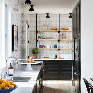 オースティンの北欧スタイルのおしゃれなダイニングキッチン (アイランドなし、アンダーカウンターシンク、シェーカースタイル扉のキャビネット、黒いキャビネット、大理石カウンター、白いキッチンパネル、サブウェイタイルのキッチンパネル、シルバーの調理設備、淡色無垢フローリング) の写真
