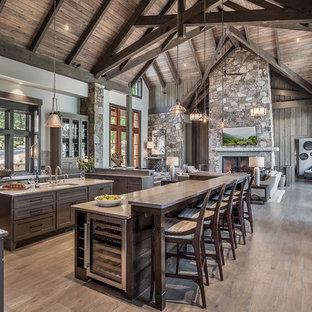 На фото: кухня-гостиная в стиле рустика с врезной раковиной, стеклянными фасадами, коричневыми фасадами, фартуком с окном, техникой из нержавеющей стали, двумя и более островами, серой столешницей и светлым паркетным полом с