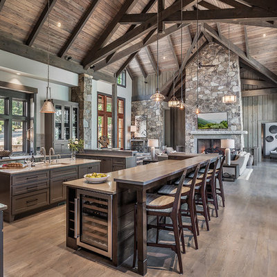 Example of a mountain style light wood floor open concept kitchen design in Other with an undermount sink, brown cabinets, window backsplash, stainless steel appliances, two islands, gray countertops and recessed-panel cabinets