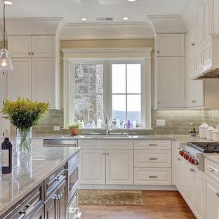 Ispirazione per una grande cucina abitabile classica con lavello sottopiano, ante con bugna sagomata, ante bianche, top in granito, paraspruzzi verde, paraspruzzi in gres porcellanato, elettrodomestici in acciaio inossidabile, pavimento in legno massello medio e isola