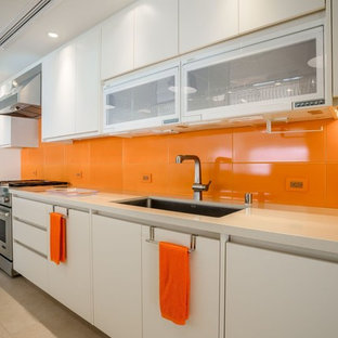 This is an example of a mid-sized contemporary single-wall separate kitchen in Hawaii with an undermount sink, flat-panel cabinets, white cabinets, quartz benchtops, orange splashback, porcelain splashback, stainless steel appliances, porcelain floors, no island and beige floor.