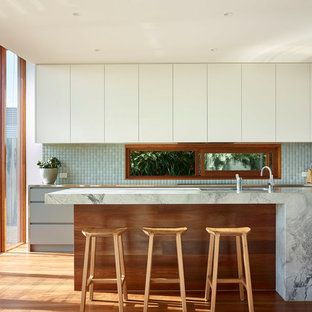 Mid-sized contemporary galley kitchen in Brisbane with an undermount sink, flat-panel cabinets, white cabinets, granite benchtops, green splashback, ceramic splashback, black appliances, medium hardwood floors, with island and brown floor.
