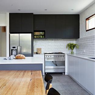 Modelo de cocina comedor en U, actual, grande, con fregadero bajoencimera, salpicadero blanco, electrodomésticos de acero inoxidable, suelo de terrazo, una isla, suelo multicolor y encimeras blancas