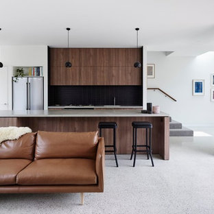 Design ideas for a contemporary galley open plan kitchen in Melbourne with flat-panel cabinets, dark wood cabinets, black splashback, stainless steel appliances, concrete floors, with island, grey floor and grey benchtop.