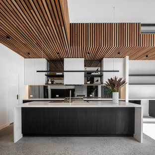 Large contemporary galley open plan kitchen in Melbourne with flat-panel cabinets, white cabinets, mirror splashback, stainless steel appliances, concrete floors, with island, grey floor, grey benchtop, a double-bowl sink, solid surface benchtops and grey splashback.
