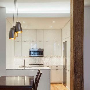 ニューヨークの小さいモダンスタイルのおしゃれなキッチン (アンダーカウンターシンク、フラットパネル扉のキャビネット、白いキャビネット、大理石カウンター、白いキッチンパネル、大理石の床、シルバーの調理設備の、淡色無垢フローリング、黄色い床) の写真