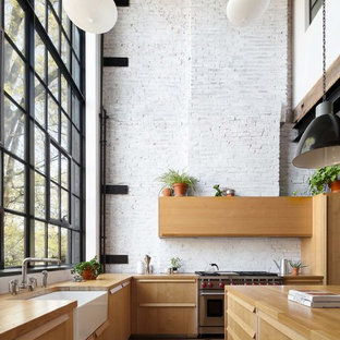 Large industrial eat-in kitchen designs - Large urban l-shaped brown floor and dark wood floor eat-in kitchen photo in New York with a farmhouse sink, flat-panel cabinets, wood countertops, white backsplash, brick backsplash, stainless steel appliances, an island, medium tone wood cabinets and brown countertops