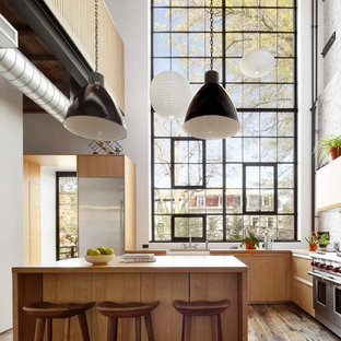 Cette image montre une grande cuisine américaine urbaine avec un placard à porte plane, des portes de placard marrons, une crédence blanche, un sol en bois brun et un îlot central.