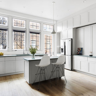 Huge transitional eat-in kitchen pictures - Eat-in kitchen - huge transitional u-shaped light wood floor and beige floor eat-in kitchen idea in New York with a drop-in sink, flat-panel cabinets, white cabinets, granite countertops, white backsplash, ceramic backsplash, stainless steel appliances, an island and green countertops