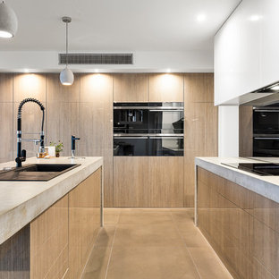 Contemporary kitchen inspiration - Example of a trendy limestone floor and gray floor kitchen design in Melbourne with a double-bowl sink, recessed-panel cabinets, light wood cabinets, concrete countertops, black backsplash, glass sheet backsplash and an island