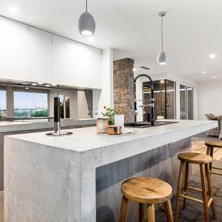 Immagine di una cucina design di medie dimensioni con ante in legno chiaro, top in cemento, paraspruzzi nero, pavimento in pietra calcarea, isola, pavimento grigio, lavello a vasca singola, ante lisce, top grigio e paraspruzzi a finestra