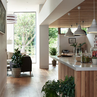 Inspiration for a mid-sized contemporary single-wall open plan kitchen in Cambridgeshire with flat-panel cabinets, white cabinets, recycled glass benchtops, white splashback, ceramic splashback, stainless steel appliances, medium hardwood floors, with island and multi-coloured benchtop.
