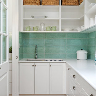 This is an example of a mid-sized transitional l-shaped kitchen pantry in Perth with an undermount sink, shaker cabinets, white cabinets, green splashback, stainless steel appliances, medium hardwood floors, no island, brown floor and white benchtop.