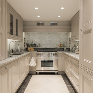 Traditional galley separate kitchen in London with an undermount sink, recessed-panel cabinets, beige cabinets, grey splashback, subway tile splashback, stainless steel appliances and no island.
