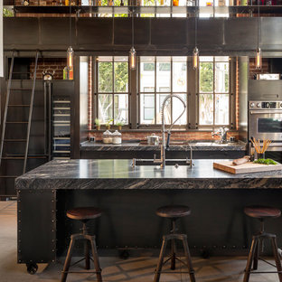 Eat-in kitchen - mid-sized industrial galley concrete floor eat-in kitchen idea in San Francisco with an island, flat-panel cabinets, stainless steel cabinets, marble countertops, stainless steel appliances and an undermount sink