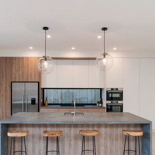 Inspiration for a contemporary galley kitchen in Melbourne with an undermount sink, flat-panel cabinets, medium wood cabinets, window splashback, stainless steel appliances, bamboo floors, with island, beige floor and grey benchtop.