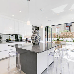 Design ideas for a contemporary kitchen/diner in London with flat-panel cabinets, white cabinets, mirror splashback, black appliances, an island and white floors.