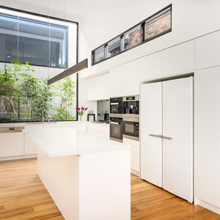 Mid-sized contemporary l-shaped kitchen in Sydney with a drop-in sink, flat-panel cabinets, white cabinets, stainless steel appliances, medium hardwood floors, multiple islands, brown floor, white benchtop, grey splashback and glass sheet splashback.