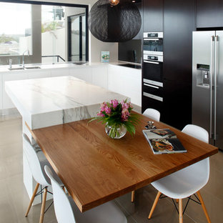 Photo of a medium sized contemporary l-shaped enclosed kitchen in Sydney with flat-panel cabinets, black cabinets, marble worktops, glass sheet splashback, stainless steel appliances, porcelain flooring and an island.