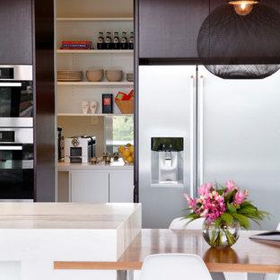 Idées déco pour une cuisine moderne en L fermée et de taille moyenne avec un évier encastré, un placard à porte plane, des portes de placard noires, un plan de travail en marbre, un électroménager en acier inoxydable, un sol en carrelage de porcelaine et un îlot central.