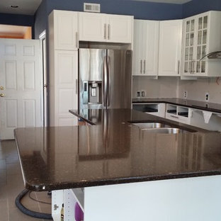 Design ideas for a large contemporary u-shaped open plan kitchen in Austin with an undermount sink, glass-front cabinets, white cabinets, quartz benchtops, stainless steel appliances, ceramic floors and with island.