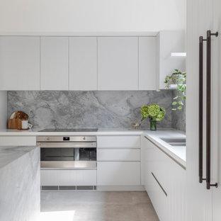 シドニーの中くらいのモダンスタイルのおしゃれなキッチン (アンダーカウンターシンク、白いキャビネット、大理石カウンター、グレーのキッチンパネル、大理石のキッチンパネル、シルバーの調理設備、セラミックタイルの床、ベージュの床、グレーのキッチンカウンター) の写真