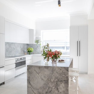 Photo of a mid-sized modern l-shaped open plan kitchen in Sydney with an undermount sink, white cabinets, marble benchtops, grey splashback, marble splashback, stainless steel appliances, ceramic floors, with island, beige floor and grey benchtop.