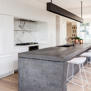 Inspiration for a contemporary galley kitchen in Sydney with an undermount sink, flat-panel cabinets, white cabinets, white splashback, stone slab splashback, panelled appliances, light hardwood floors, with island, beige floor and white benchtop.