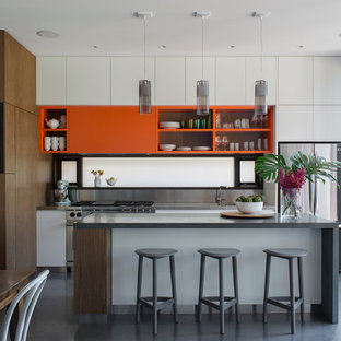 Mid-sized contemporary eat-in kitchen ideas - Example of a mid-sized trendy l-shaped concrete floor eat-in kitchen design in Sydney with an integrated sink, flat-panel cabinets, medium tone wood cabinets, granite countertops, metallic backsplash, stainless steel appliances and an island