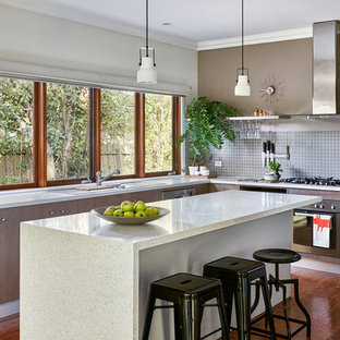 Design ideas for a mid-sized contemporary u-shaped open plan kitchen in Melbourne with flat-panel cabinets, light wood cabinets, solid surface benchtops, grey splashback, with island, white benchtop, an undermount sink, ceramic splashback, stainless steel appliances, medium hardwood floors and brown floor.
