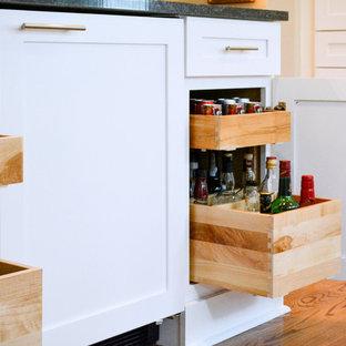 他の地域の中サイズのエクレクティックスタイルのおしゃれなキッチン (アンダーカウンターシンク、シェーカースタイル扉のキャビネット、グレーのキャビネット、クオーツストーンカウンター、グレーのキッチンパネル、ガラスタイルのキッチンパネル、シルバーの調理設備の、無垢フローリング、茶色い床) の写真