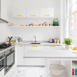 Photo of a small contemporary u-shaped enclosed kitchen in London with flat-panel cabinets, white cabinets, stainless steel appliances, white floors, ceramic flooring, a submerged sink and a breakfast bar.